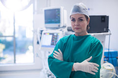 Female surgeon standing with arms crossed in operation room Royalty Free Stock Image
