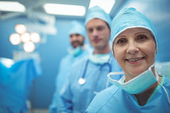Female surgeon wearing surgical mask in operation theater. At hospital Stock Image