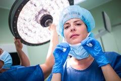 Female surgeon wearing surgical mask Stock Photo