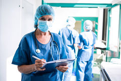 Female surgeon writing on clipboard in corridor Stock Photos