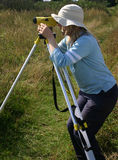 Female surveyor. Blond girl doing archaeological field surveying work with a level Royalty Free Stock Photos