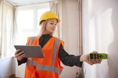 Female Surveyor With Digital Tablet Measuring Room With Laser Measure royalty free stock images