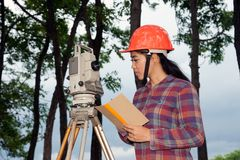 Female Surveyor or Engineer making measure on the field. Royalty Free Stock Images