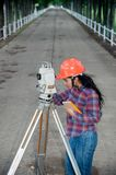 Female Surveyor or Engineer making measure on the field. Stock Photo