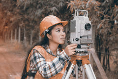 Female Surveyor or Engineer making measure by Theodolite on the street. royalty free stock photo