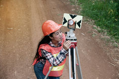 Female Surveyor or Engineer setting measure prism reflector on the street. Female Surveyor or Engineer setting measure prism reflector on the street in a field stock photography