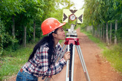Female Surveyor or Engineer setting measure prism reflector on the street. Female Surveyor or Engineer setting measure prism reflector on the street in a field royalty free stock photos