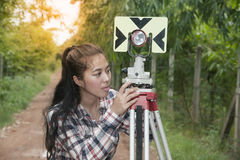 Female Surveyor or Engineer setting measure prism reflector on the street. Female Surveyor or Engineer setting measure prism reflector on the street in a field royalty free stock photo