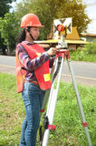 Female Surveyor or Engineer setting measure prism reflector on the street. Royalty Free Stock Photos