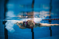 Female swimmer in action inside swimming pool. Royalty Free Stock Photo