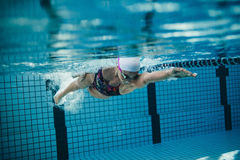 Female swimmer in action inside swimming pool. Underwater shot of female swimmer in action inside swimming pool. Young woman training in the pool Stock Photos