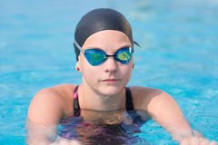 Female swimmer in blue water swimming pool. Sport woman. Portrait of a female swimmer wearing a swimming cap and goggles in blue water swimming pool. Sport Royalty Free Stock Photography