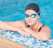 Female swimmer in blue water swimming pool. Sport woman. Portrait of a female swimmer wearing a swimming cap and goggles in blue water swimming pool. Sport Stock Image