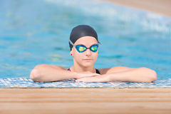 Female swimmer in blue water swimming pool. Sport woman. Portrait of a female swimmer wearing a swimming cap and goggles in blue water swimming pool. Sport Stock Photography