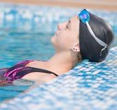 Female swimmer in blue water swimming pool. Sport woman. Portrait of a female swimmer wearing a swimming cap and goggles in blue water swimming pool. Sport Stock Image