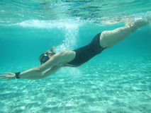 Female swimmer diving underwater in ocean Royalty Free Stock Photography