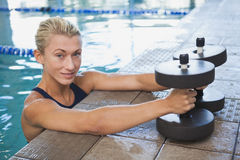 Female swimmer with foam dumbbells in swimming pool Stock Photography