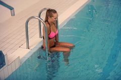 A female swimmer going into indoor sport swimming pool. smiling girl in pink sweimsuit Royalty Free Stock Photography