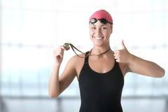 Female Swimmer Holding Medal. Female swimmer holding her medal after winning Royalty Free Stock Image