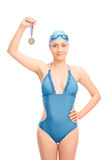 Female swimmer holding a medal Stock Photos