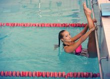 A female swimmer in indoor sport swimming pool. girl in pink sweimsuit training. Stock Photos