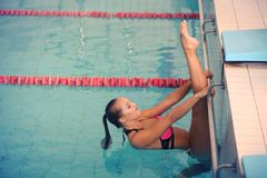 A female swimmer in indoor sport swimming pool. girl in pink sweimsuit training Stock Image