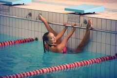 A female swimmer in indoor sport swimming pool. smiling girl in pink sweimsuit. Looking to camera Royalty Free Stock Photography