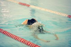 A female swimmer in indoor sport swimming pool trying to dive. Royalty Free Stock Image