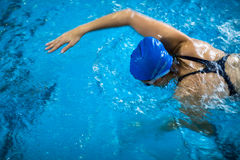 Female swimmer in an indoor swimming pool - doing crawl Stock Image