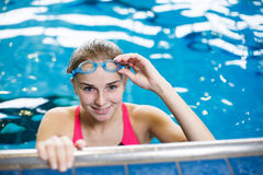 Female swimmer in an indoor swimming pool. Looking at the camera, smiling wholeheartedly shallow DOF; color toned image Royalty Free Stock Images