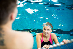 Female swimmer in an indoor swimming pool , talking to a friend Stock Images