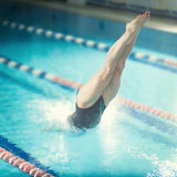 Female swimmer, that jumping into indoor swimming. Portrait of a female swimmer, that jumping and diving into indoor sport swimming pool. Sporty woman Royalty Free Stock Photos