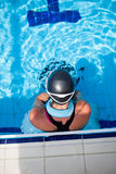 Female swimmer at pool edge. Female freediver with neck weight and monofin at edge of outdoor swimming pool stock image