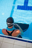 Female swimmer at pool edge. Female freediver with neck weight and monofin at edge of outdoor swimming pool royalty free stock photos