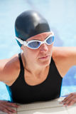 Female swimmer at pool edge Stock Image