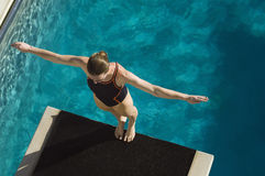 Female Swimmer Ready To Dive. High angle view of a female swimmer ready to dive while standing at the edge of the springboard stock image