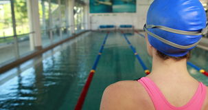 Female swimmer ready to dive into swimming pool stock footage