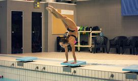 A female swimmer, that ready to jump into indoor sport swimming pool. standing on arms with legs up. Behind head Stock Image