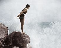 Female swimmer on rock above crashing surf royalty free stock photo