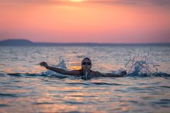 Female swimmer in sea at sunset. Silhouette portrait of female swimmer swimming in ocean at sunset over sea. Water sport and healthy lifestyle concepts Stock Images