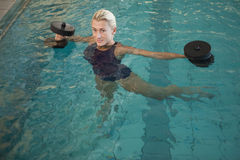 Female swimmer working out with foam dumbbells in swimming pool Stock Photography