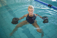 Female swimmer working out with foam dumbbells in swimming pool Stock Photos