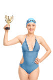 Female swimming champion holding a gold cup. Vertical shot of a female swimming champion holding a gold cup and looking at the camera isolated on white stock photos