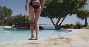 Female in swimsuit walking into the pool stock footage