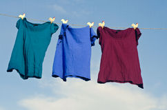 Female t-shirts on a string against blue sky Stock Photos