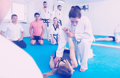 Female taekwondo instructor demonstrates receptions. For beginners in the gym stock image