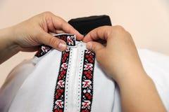 Female tailor captures shirt collar. Using pin Stock Photography