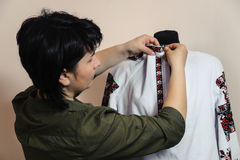 Female tailor captures shirt collar Royalty Free Stock Image
