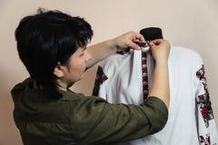 Female tailor captures shirt collar. Using pin Royalty Free Stock Image