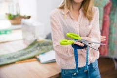 Female tailor holding measuring tape and scissors Stock Photo